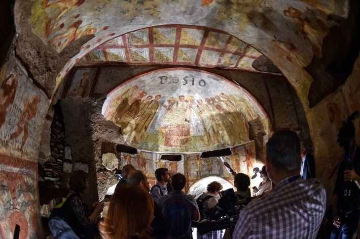Visitors admire a restored fresco in the catacombs of St. Domitilla.