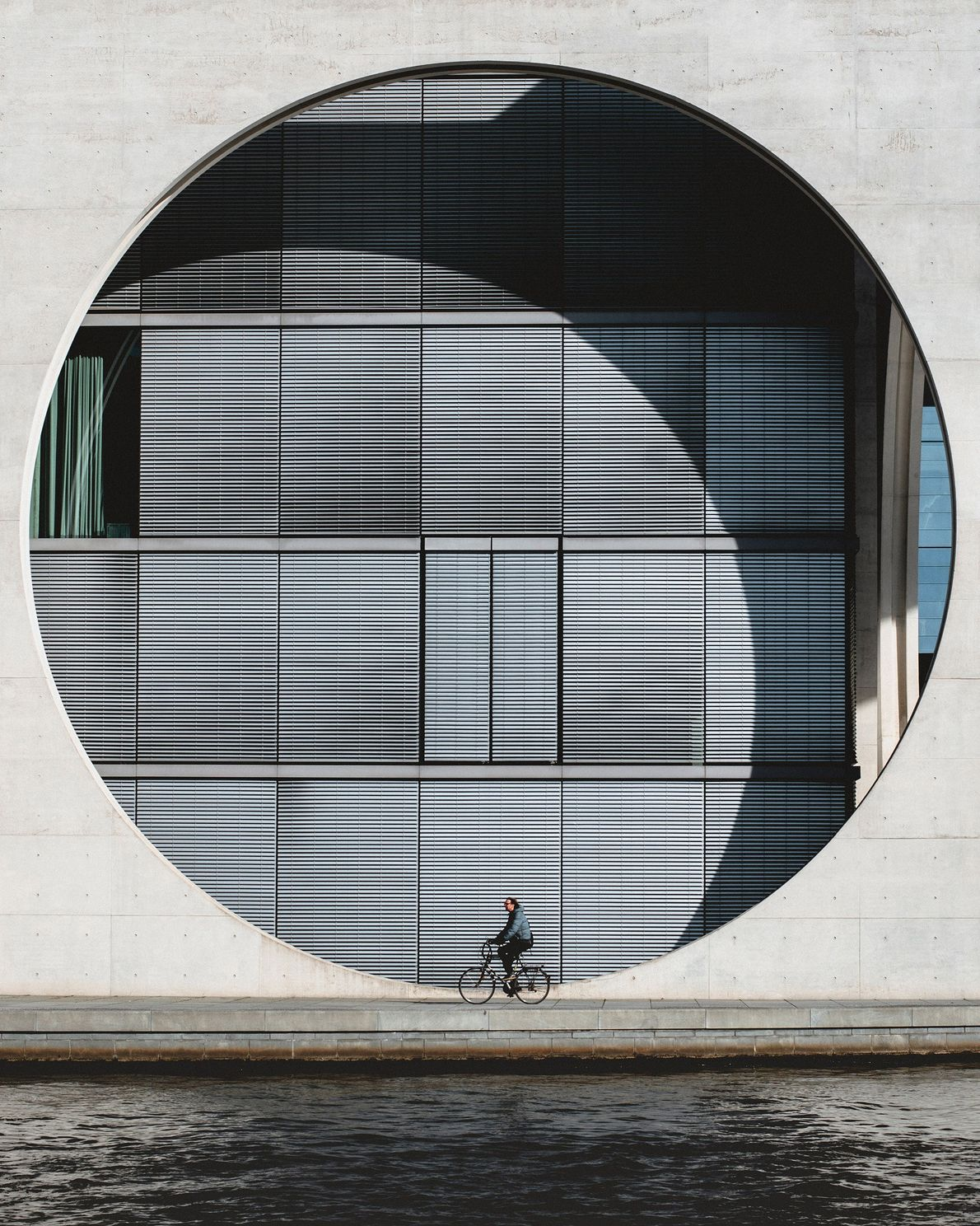 A cyclist passes by the back of the German Chancellery building in Berlin. The building's modern ...