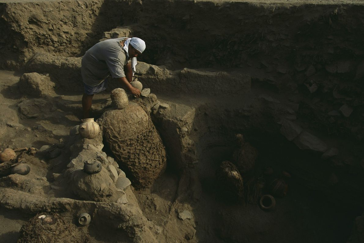 An archaeologist removes artefacts near a Inca mummy bundle. Thousands of the 500-year-old bundles contain human ...