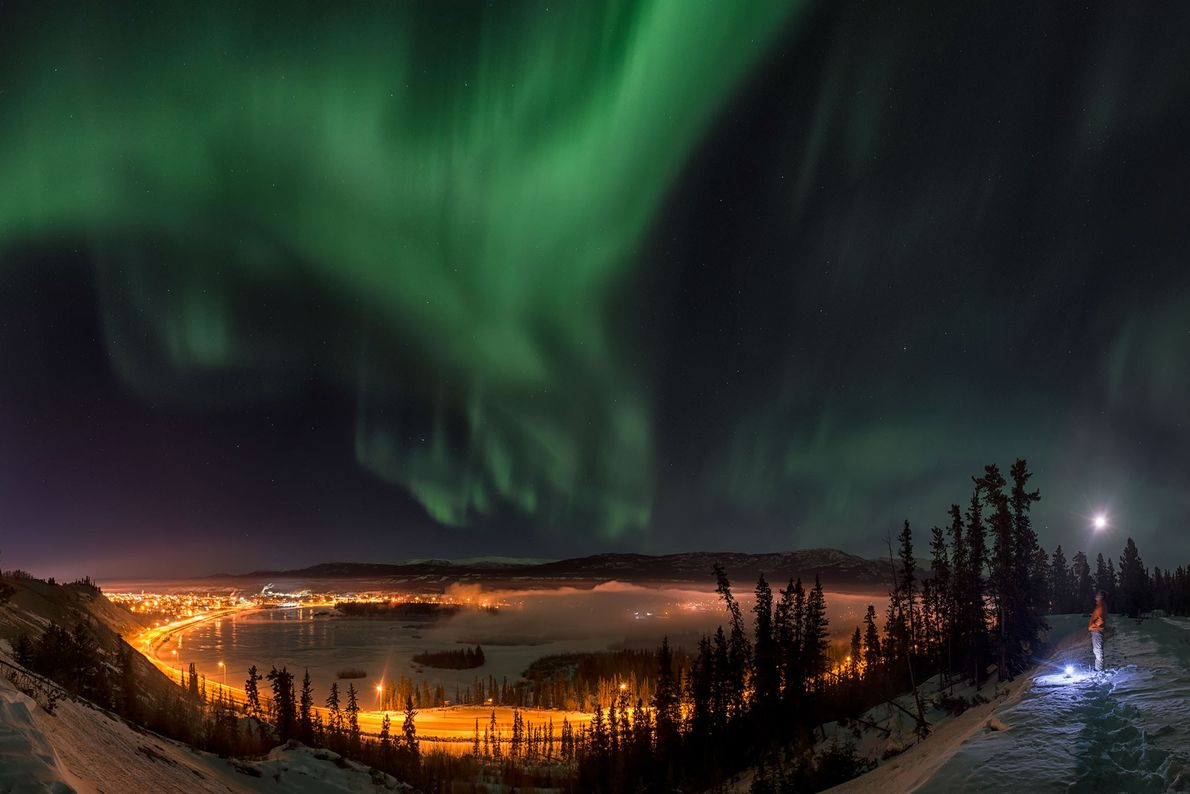 A man watches the northern lights above the city of Whitehorse in Canada's Yukon Territory.