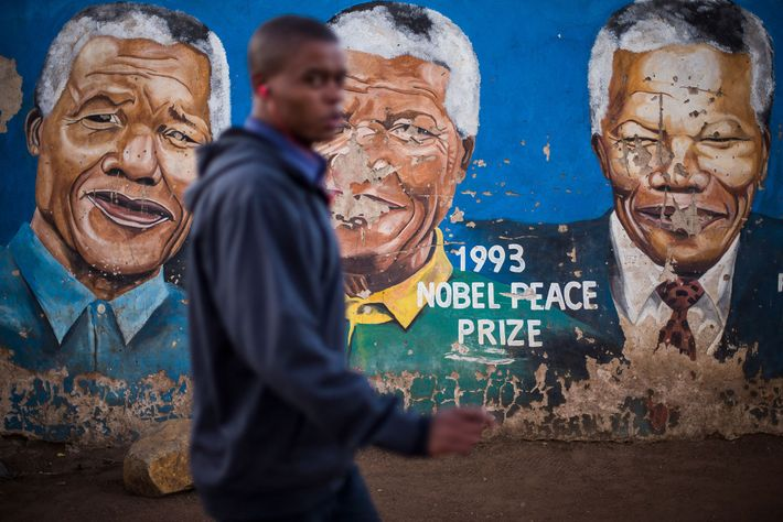 A man passes by a wall bearing several images of Nelson Mandela on Khumalo street in ...