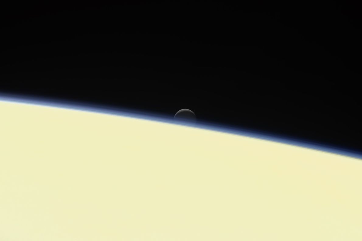 Saturn's icy moon Enceladus sinks behind the planet in a farewell portrait from NASA's Cassini spacecraft, ...