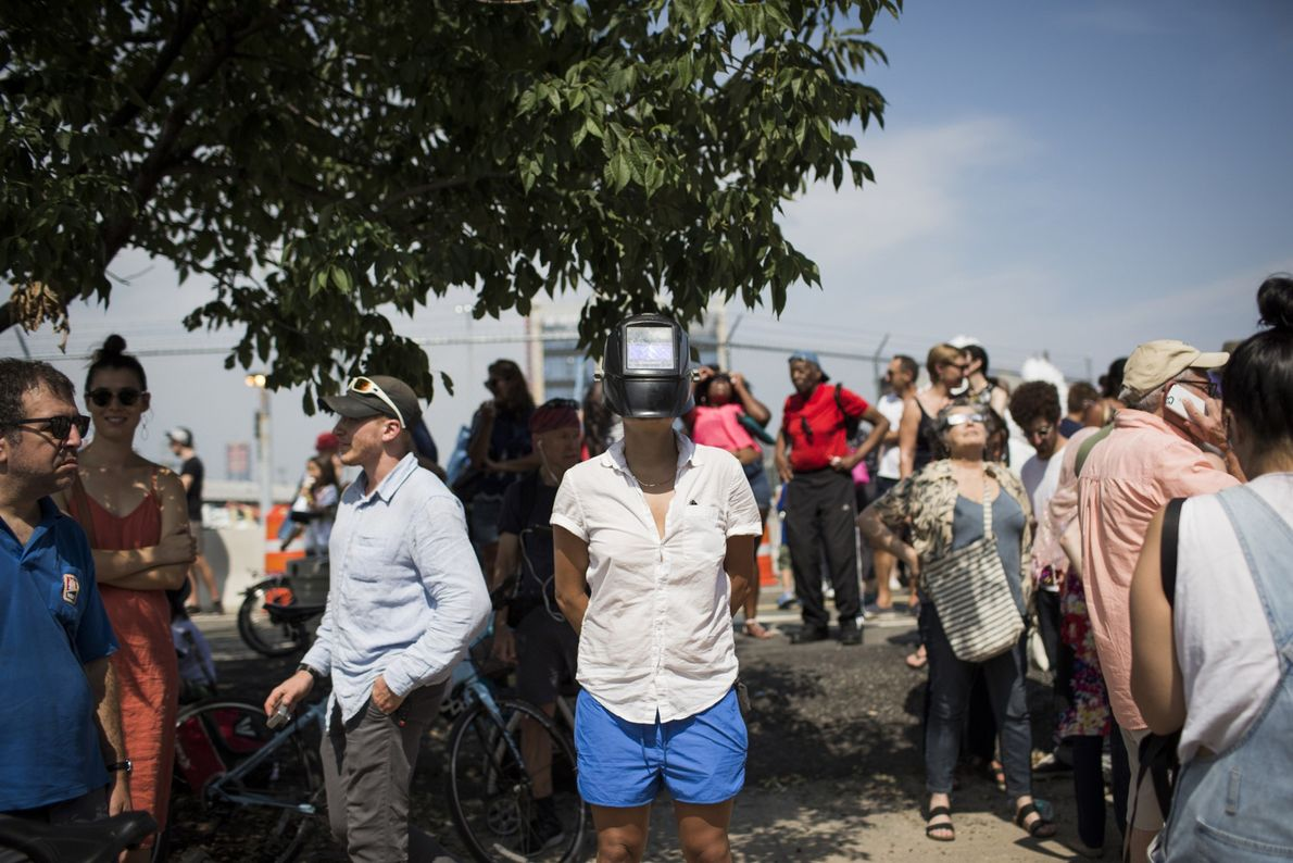 A woman wears a welding mask to protect her eyes while watching the partial eclipse from ...