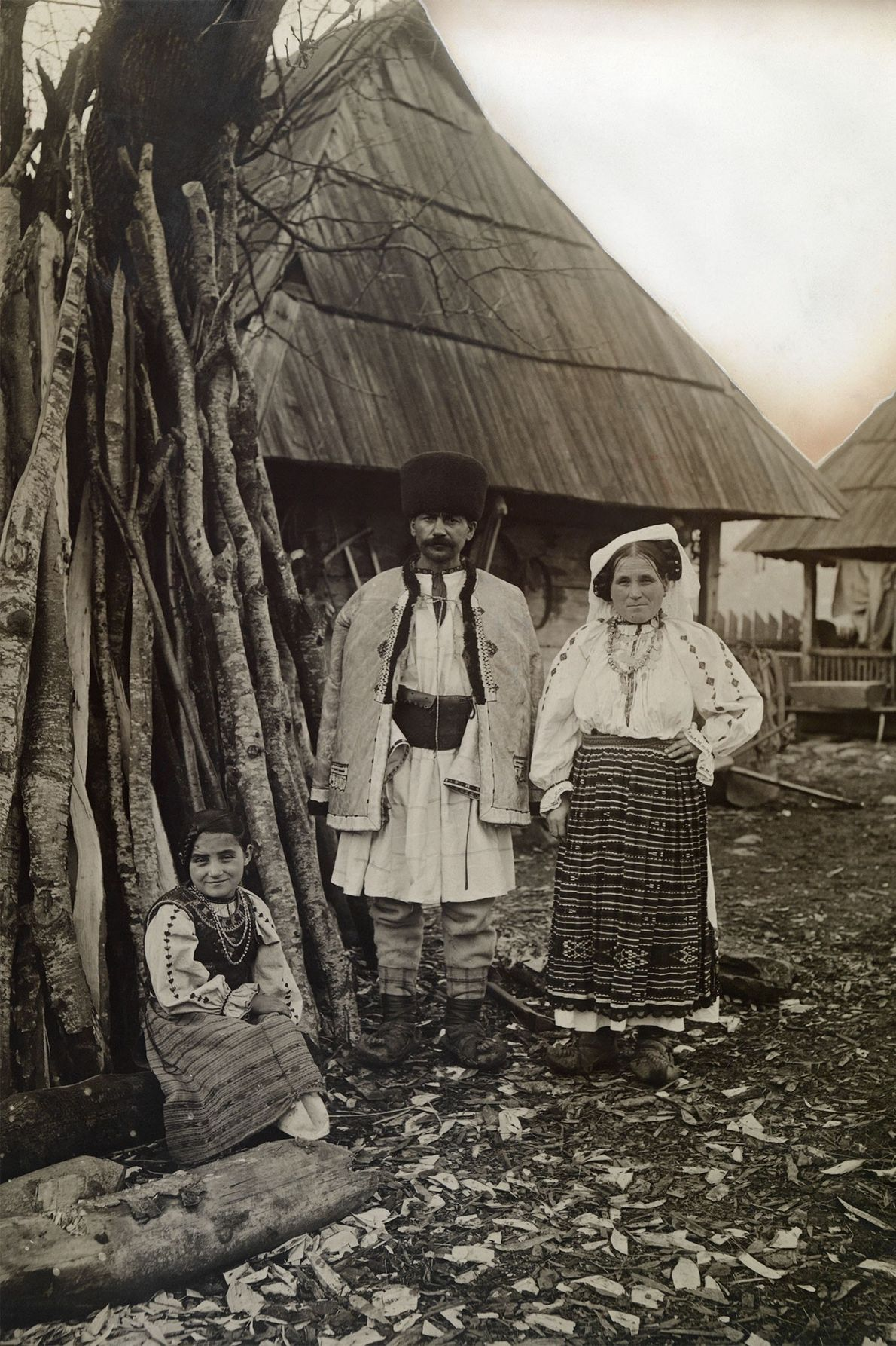 A Wallachian family stands outside their home in Transylvania in the early 1900s.
