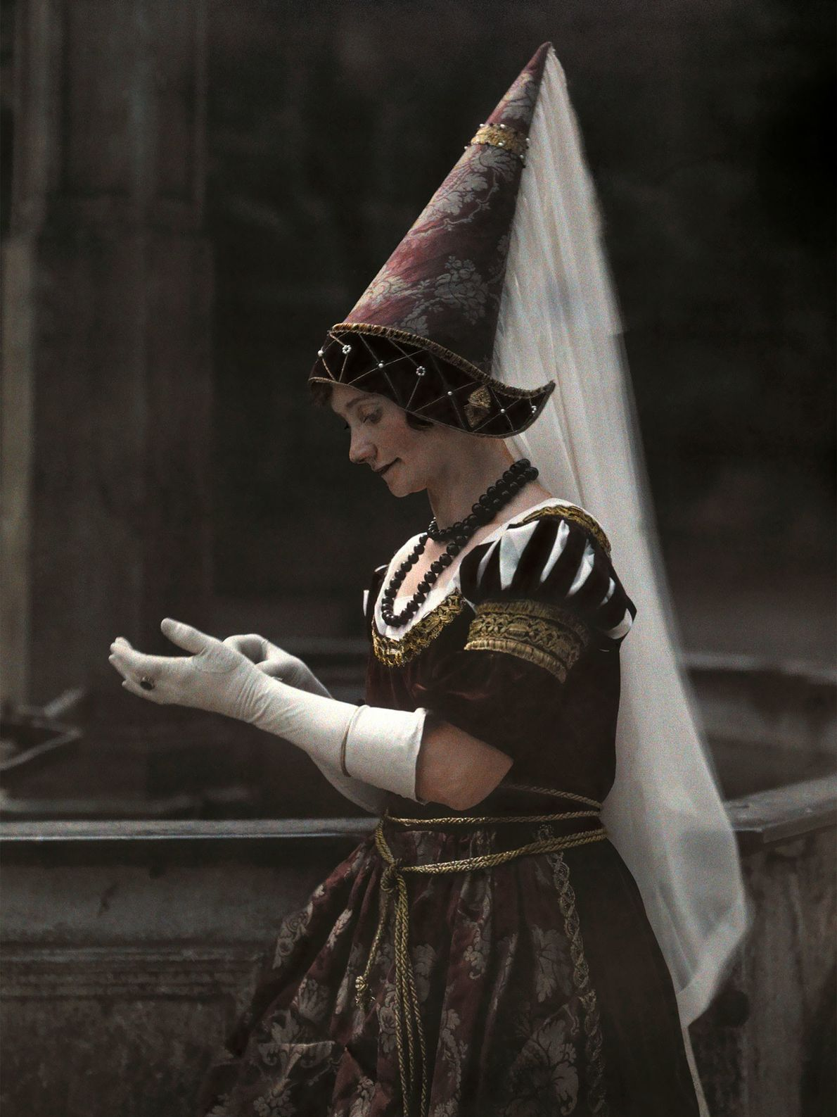 A Bavarian woman wearing a hennin, or medieval cone-shaped princess hat, in Germany adjusts her gloves ...