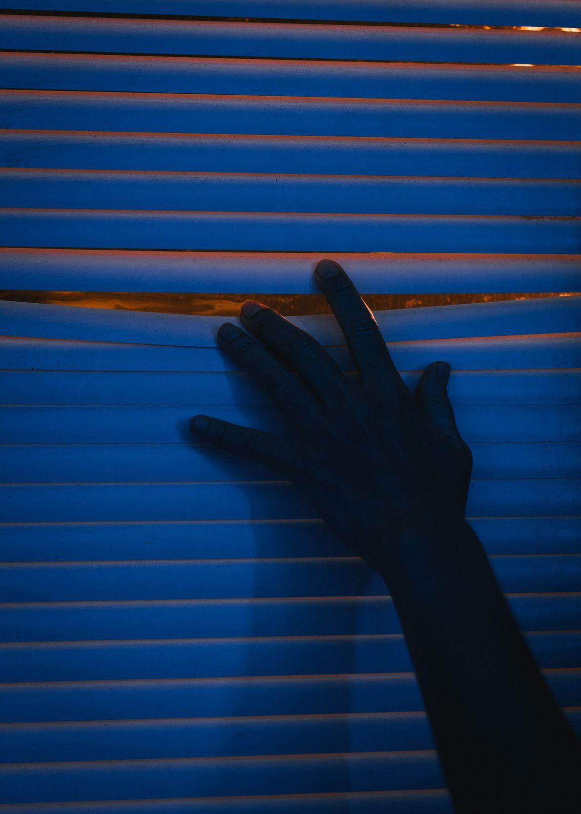 Field crew member Aline Decadi peeks through a window blind in the crew's quarters.