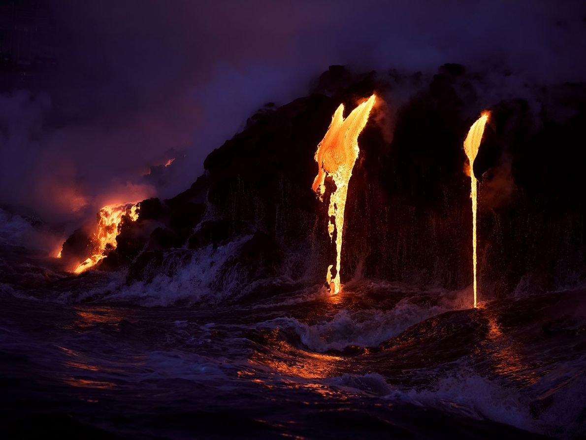 A river of lava spills into the sea at twilight in this shot, taken from a ...