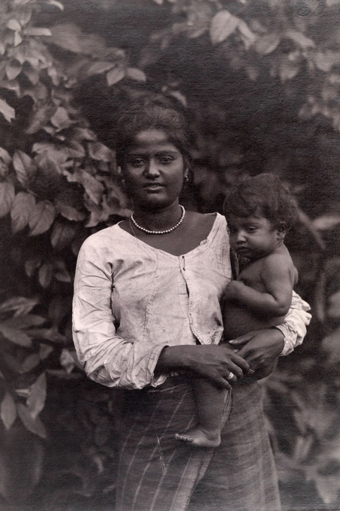 A Ceylonese mother rests a child on her hip.