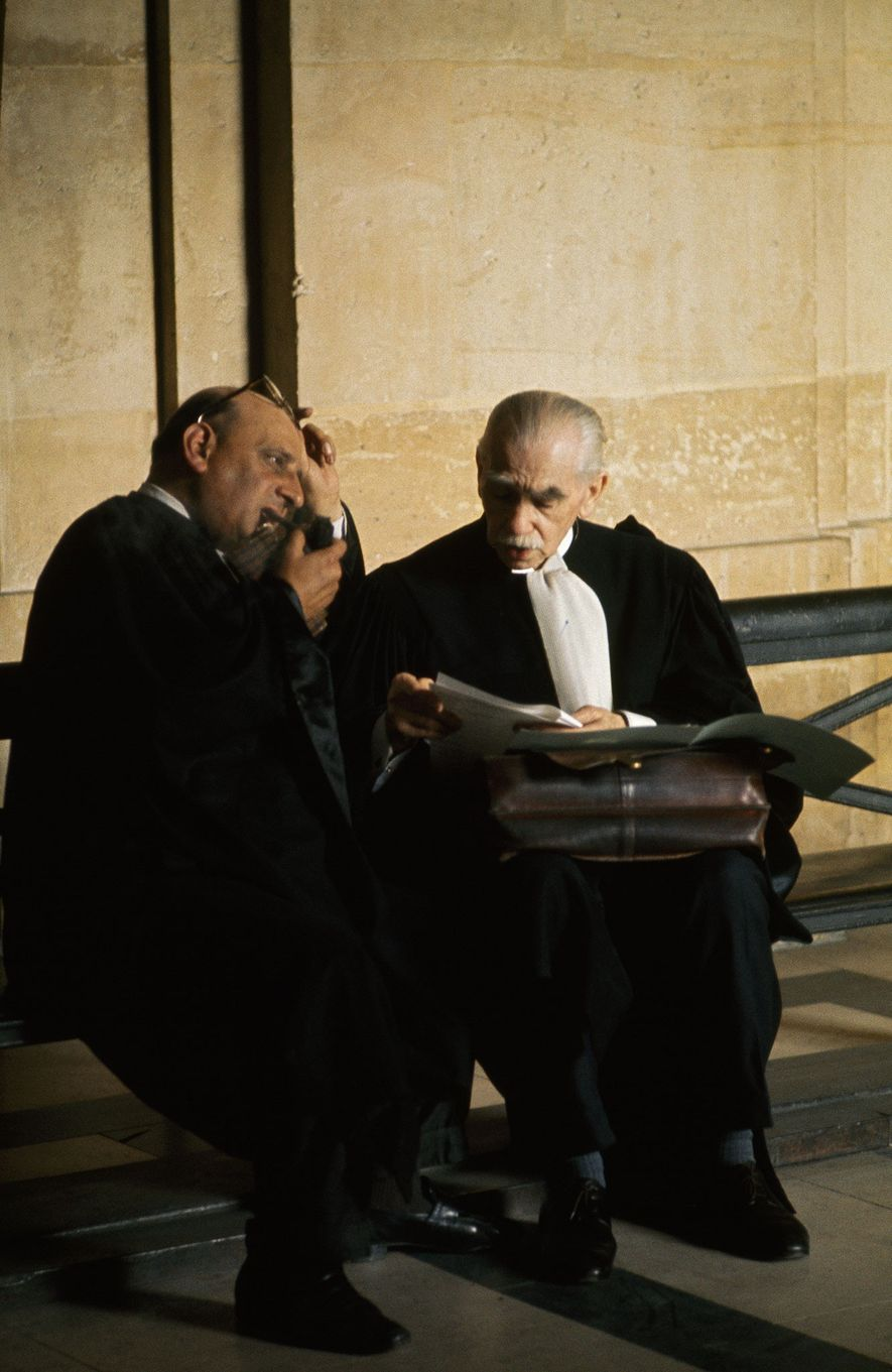 Conferring on a case, French lawyers review a thick dossier outside a courtroom in the Palais ...