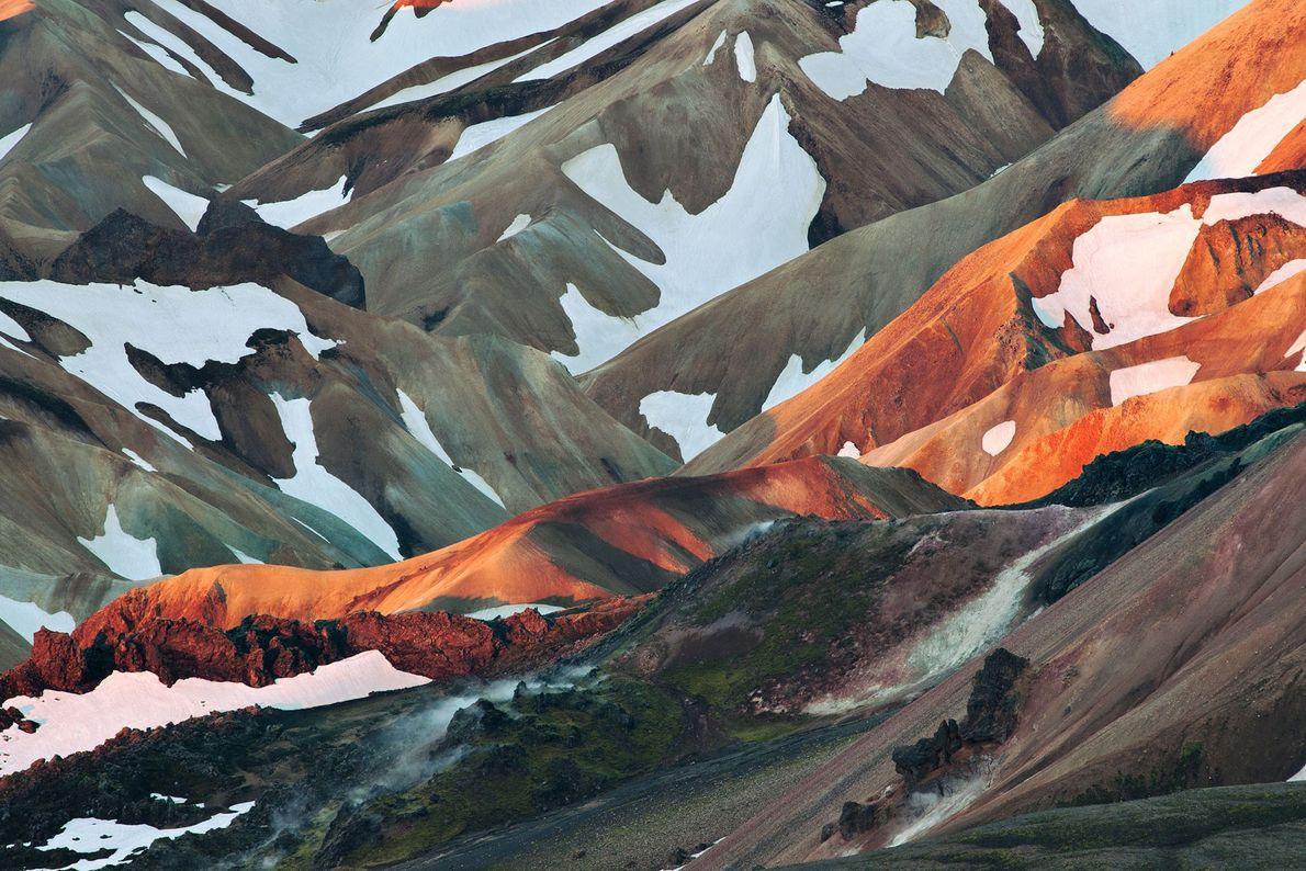 The first beams of a June day spotlight a ridge of rusty volcanic rhyolite at Landmannalaugar ...