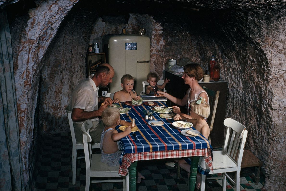 A miner and his family eat in their undergound kitchen in Coober Pedy, Australia.