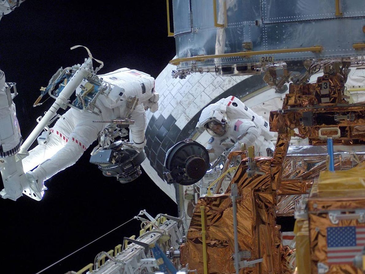 Two astronauts work in the payload bay of space shuttle Columbia in March of 2002, completing ...