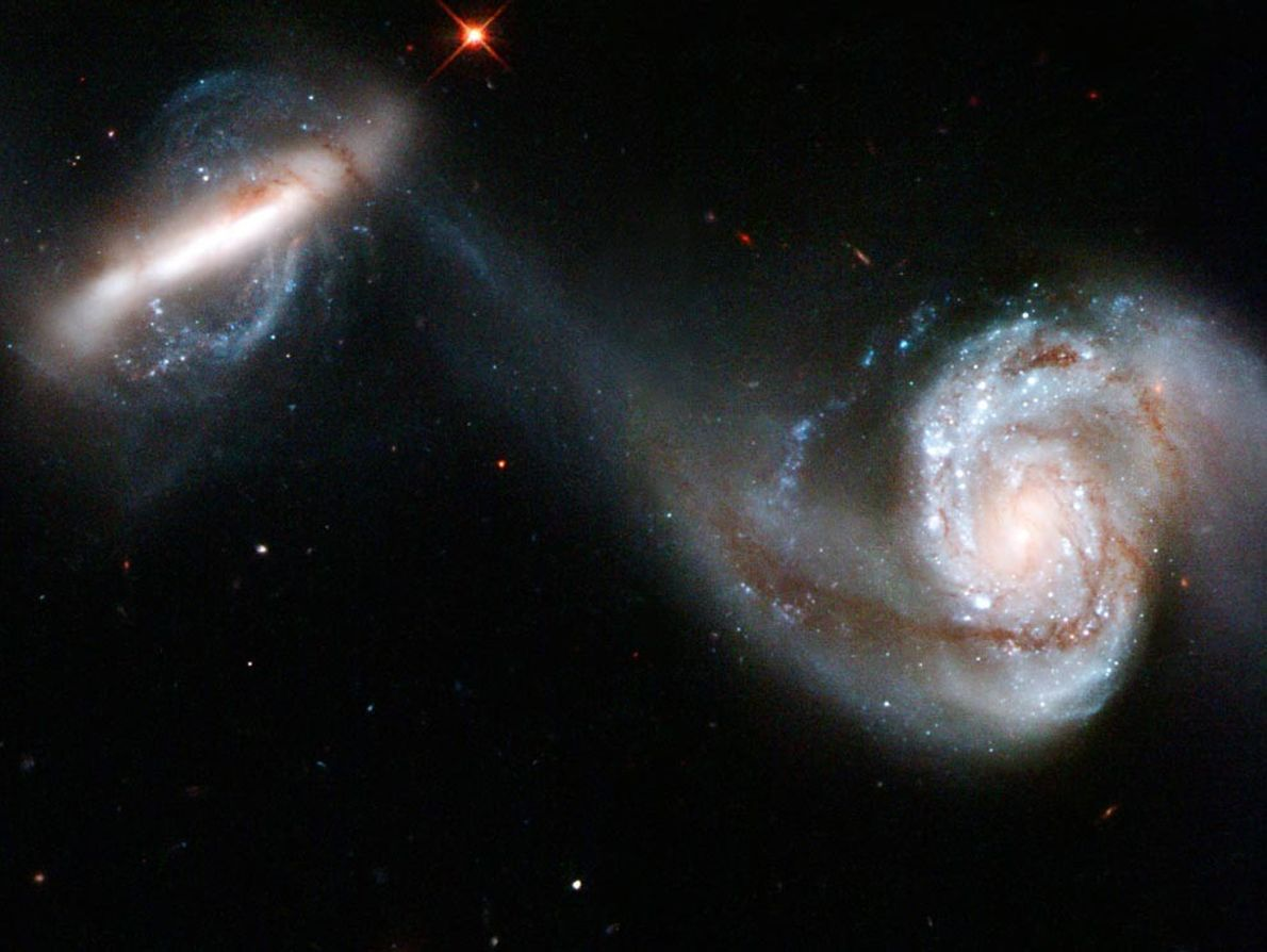 Two galaxies, known collectively as Arp 87, distort as their gravitational fields interact. The larger of ...