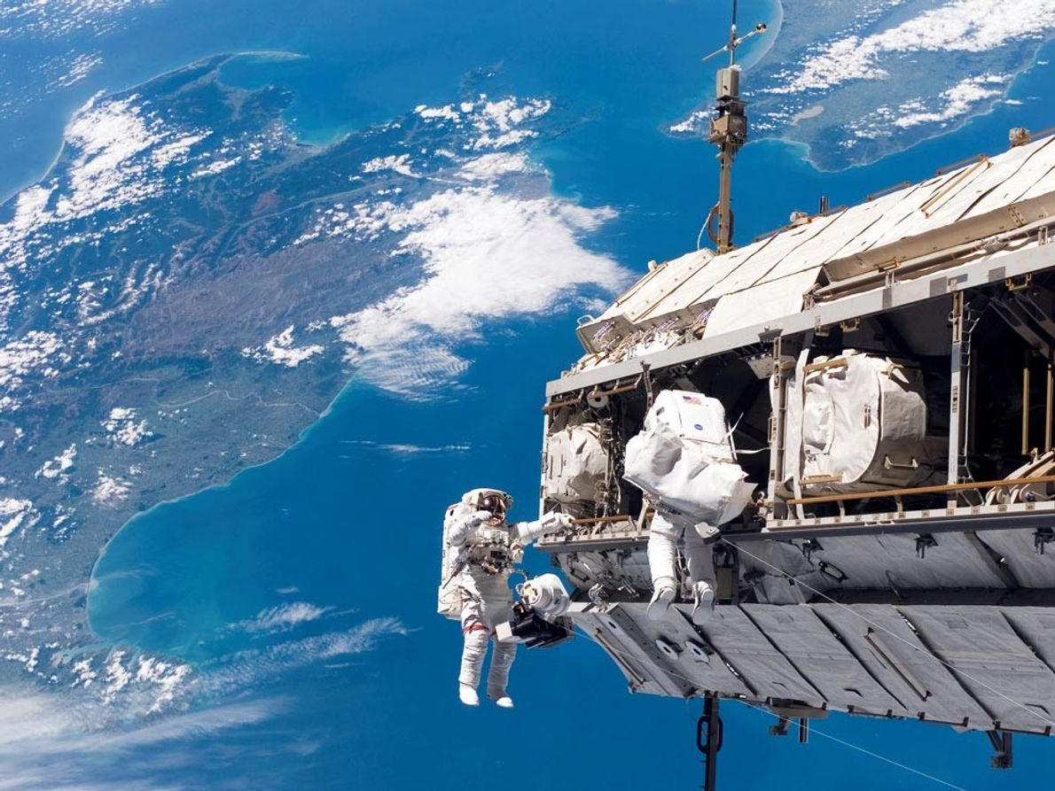 Discovery mission specialists Robert Curbeam (left) and Christer Fuglesang work on ISS construction during a spacewalk ...