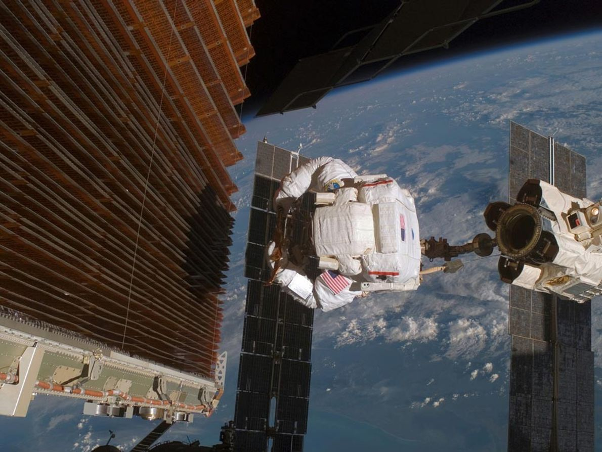 Astronaut Robert Curbeam works on the port overheard solar array wing on the International Space Station's ...