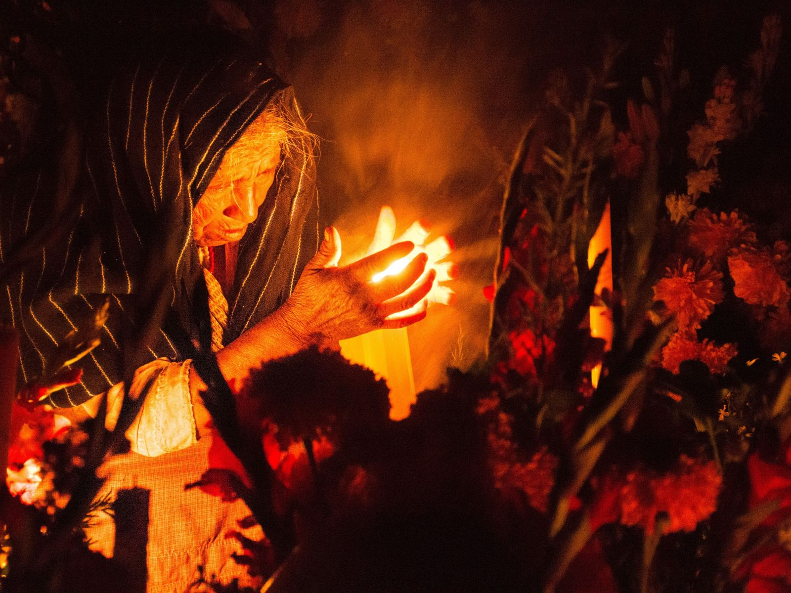 """A woman prays in a cemetary in Puebla, south-east Mexico, during Day of the Dead. """"Since ..."""