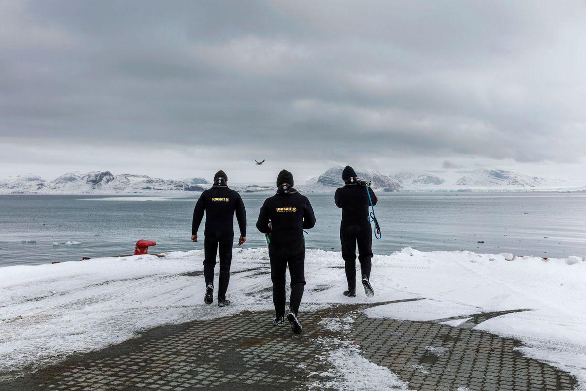 German divers Max Schwanitz (left), Philipp Fischer (right, carrying pump), and Kai Schwalfenberg (middle) perform underwater ...