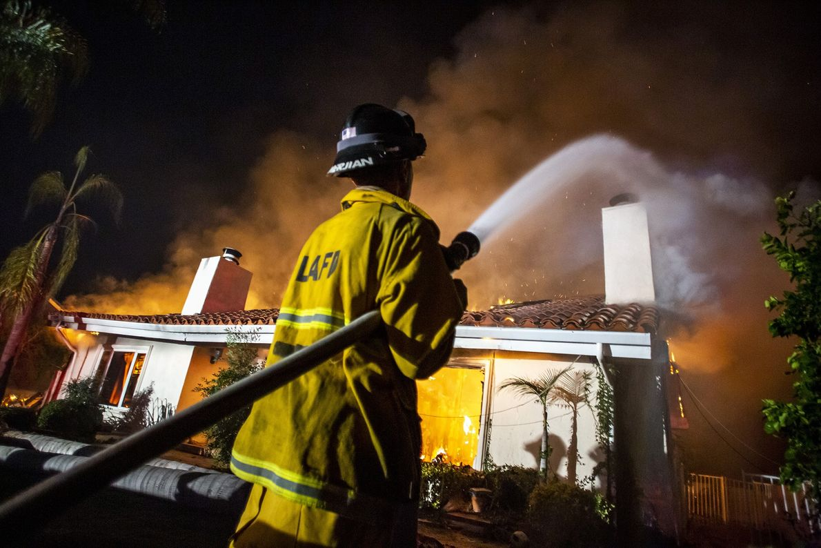Firefighters work to control a house fire caught in the Woolsey Fire in West Hills, California.