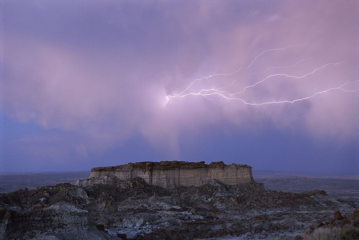 A faint trail of lighting cuts its way through evening clouds over a hilltop in Wyoming's ...