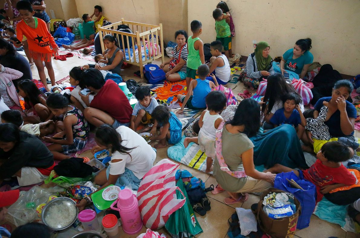 Residents living along the coastal community of Baseco seek temporary shelter at an evacuation center in ...