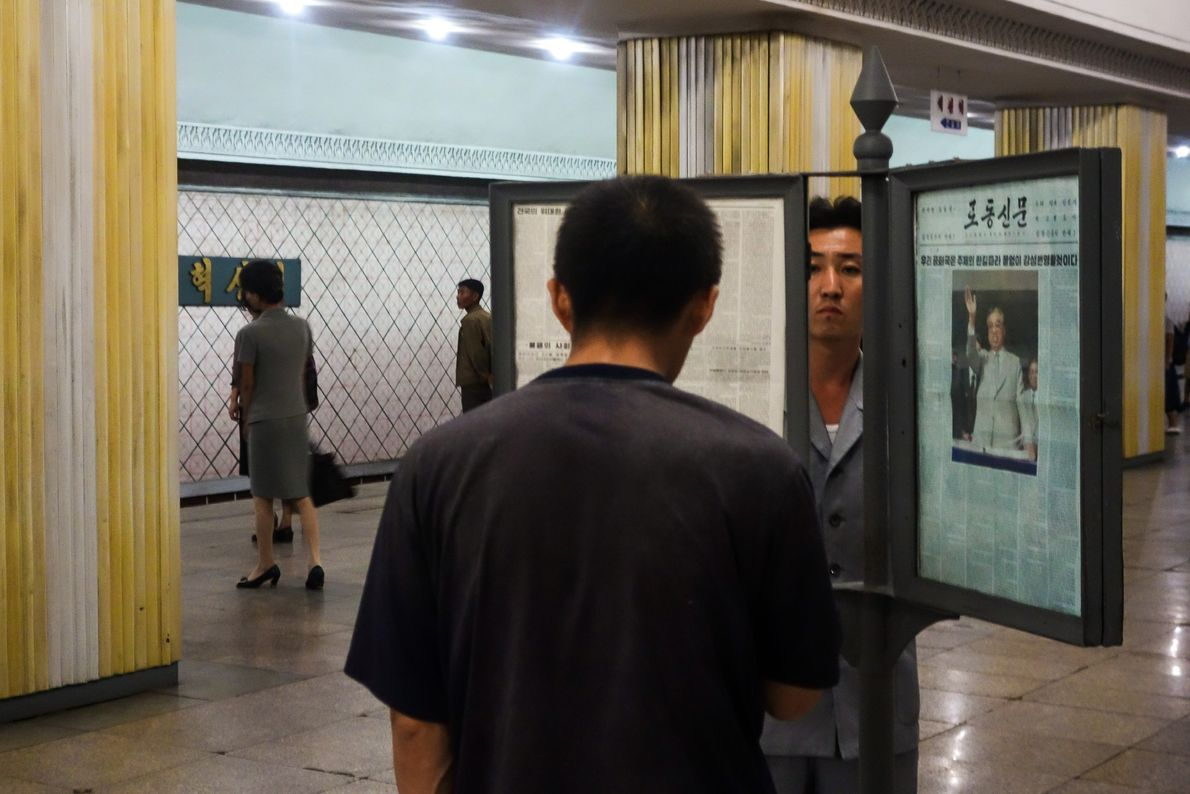 Train platforms feature framed copies of the state-run newspaper. Commuters catch up on the news while ...