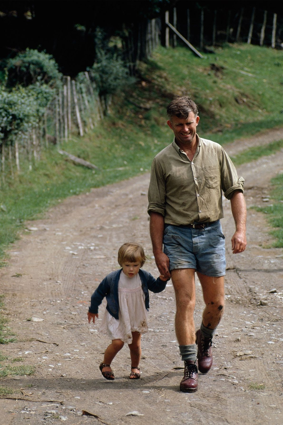 A farmer walks along a dirt road with his daughter on New Zealand's North Island in ...