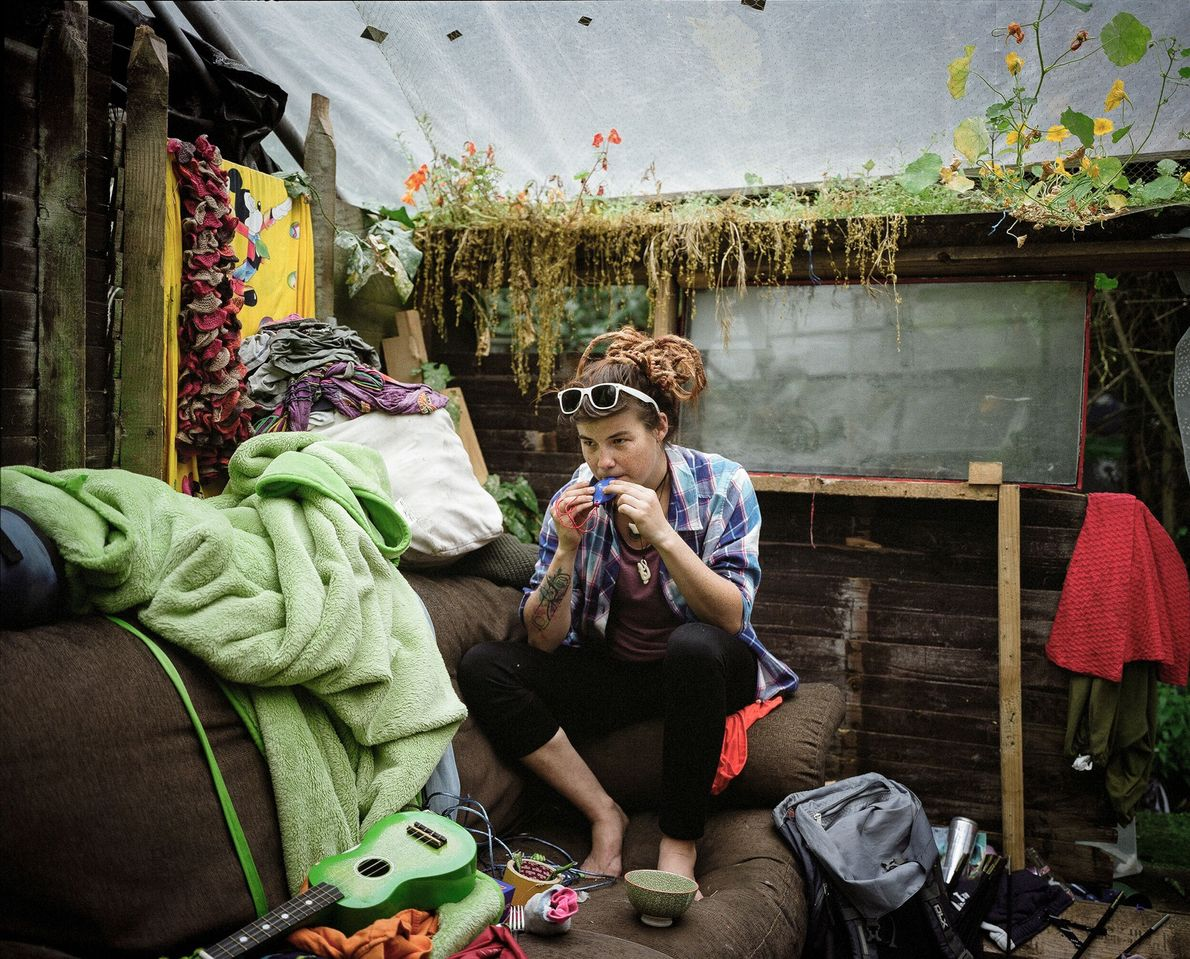 A resident sits in her living room, decorated with wild flowers.