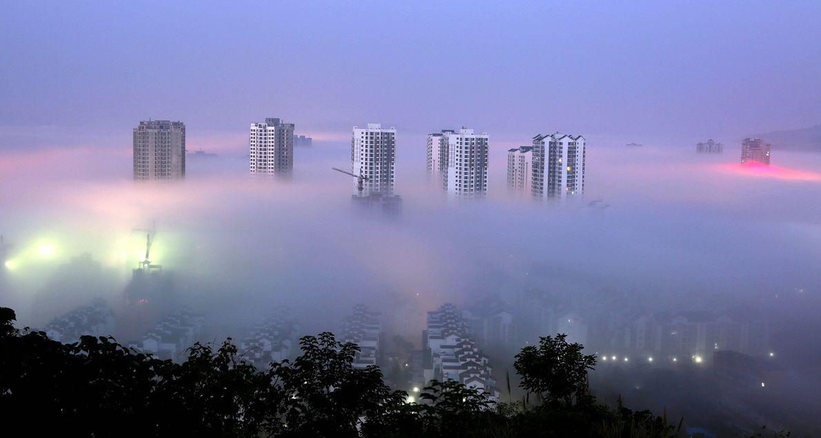 A few high-rise buildings penetrate through a stratus cloud cast over Dazu District of Chongqing, in ...