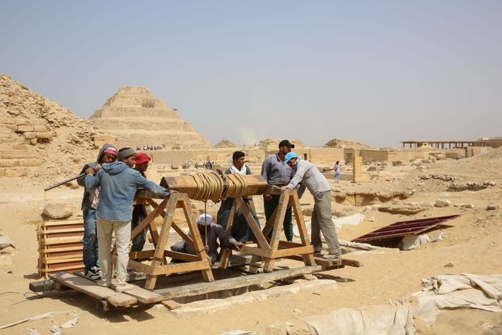Workers use a hand-cranked winch to lower tools and other gear to the mummy workshop and ...