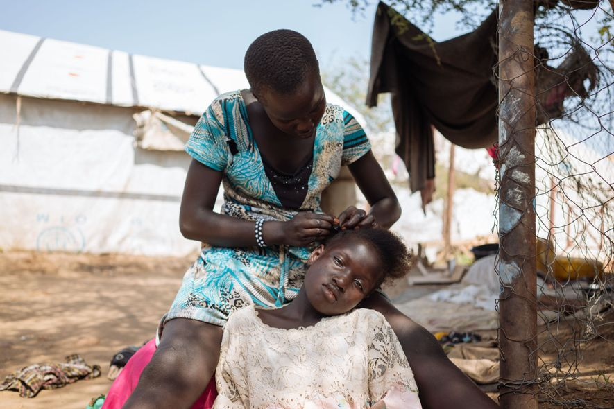 A woman does another young women's hair inside a Protection of Civilians site in South Sudan. ...