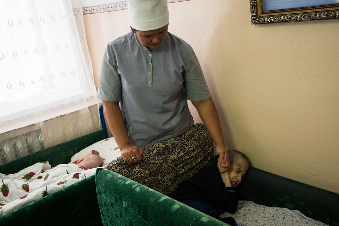 Nurse Marjan Kasenova plays with Kanat Rahimov, 15, in a ward of the Children's Centre of ...