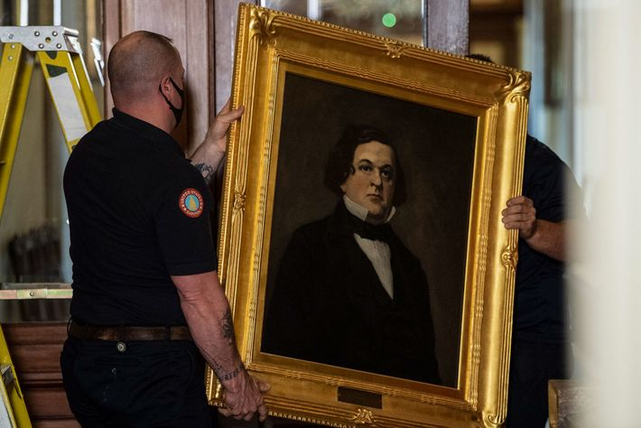 Workers remove a painting of former Confederate House Speaker Howell Cobb of Georgia from the east ...