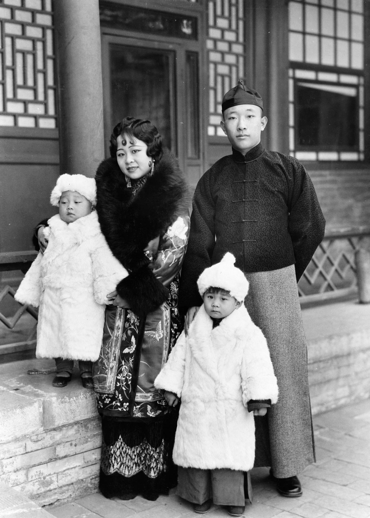 A Mongol prince and princess stand with their young children in the 1930s, wrapped in warm ...