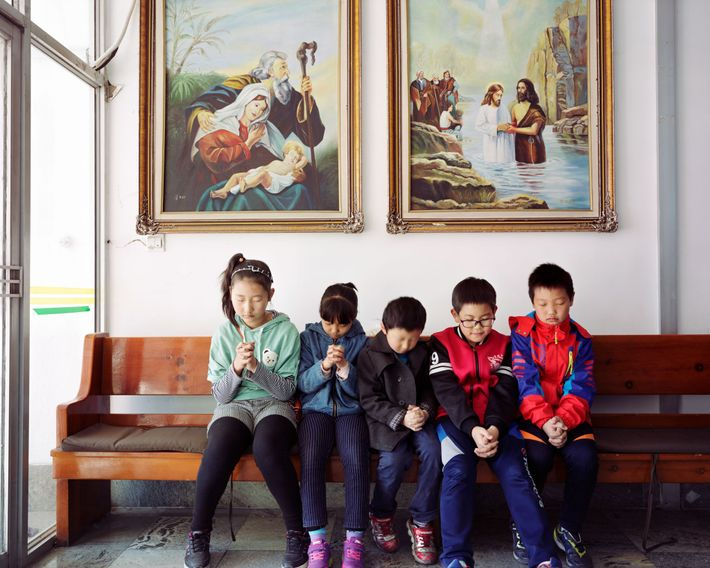Five Korean children pray in a local church in Longjing, Jilin province, China in 2017. Bordering ...