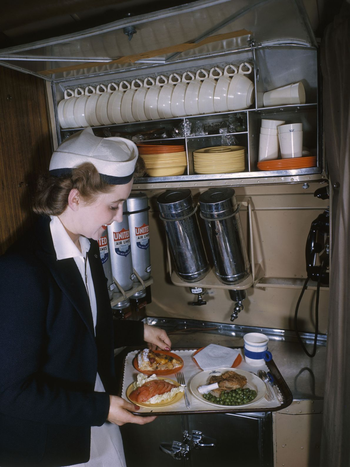 A stewardess prepares an in-flight meal, complete with dessert.