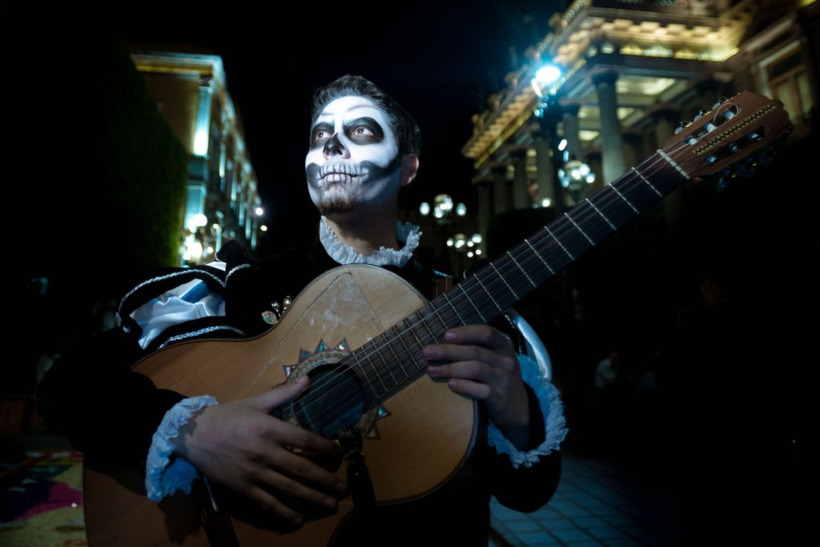 A young musician from the city of Guanajuato plays his guitar, face painted in the style ...