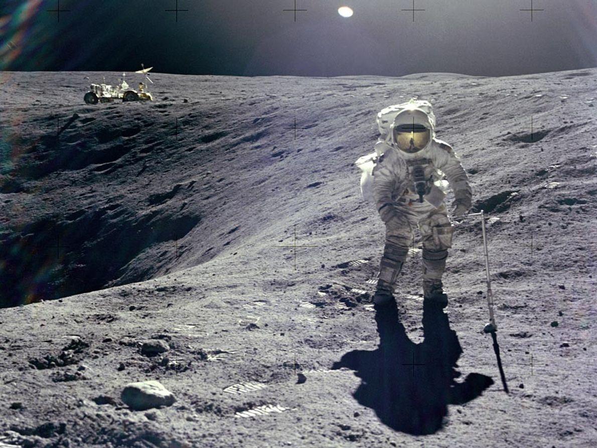 Apollo 16 lunar module pilot Charles Duke collects samples near the rim of Plum Crater, a ...