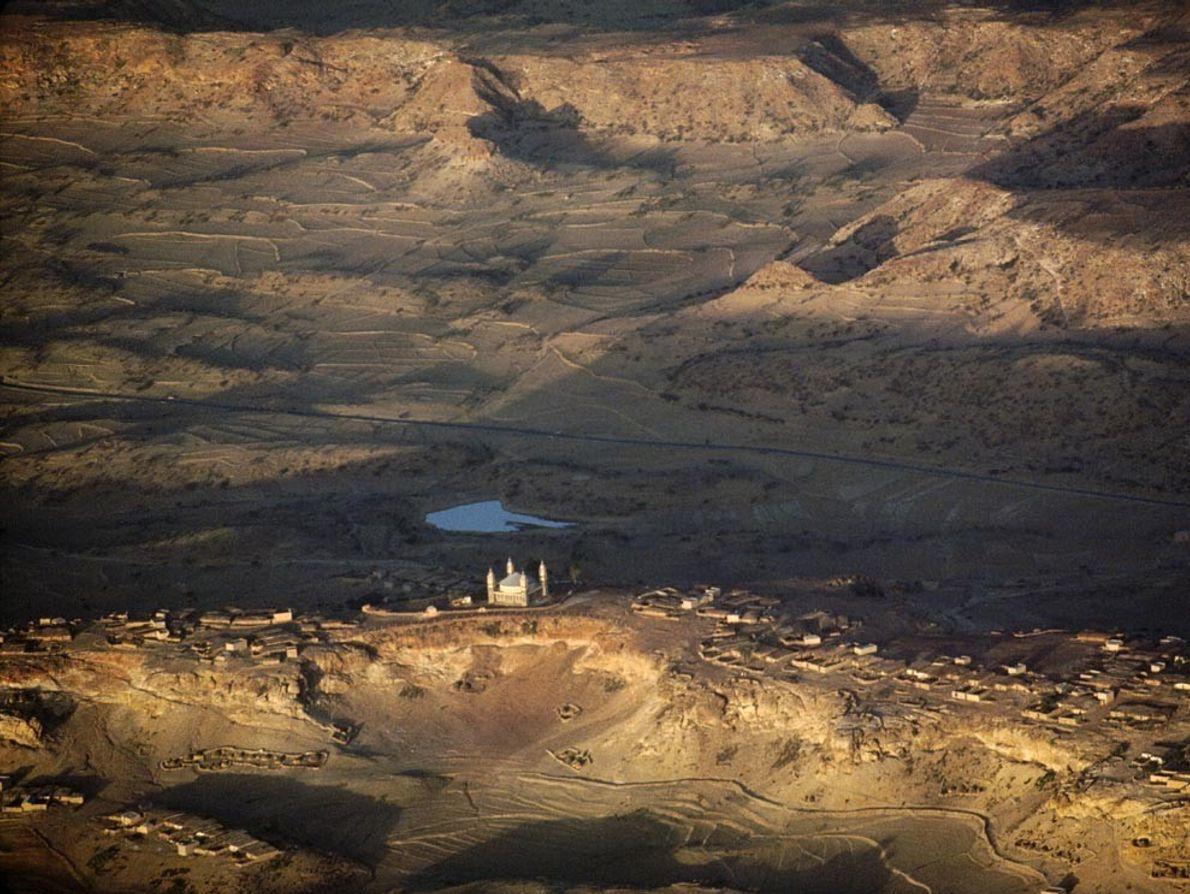 A mosque dominates the farming villages of Adi Caieh, Eritrea. Rift escarpments in the distance, now ...