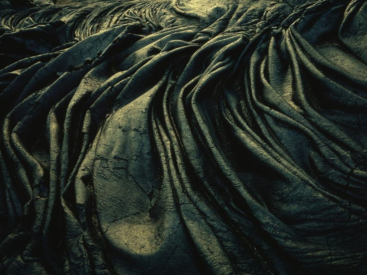 Cooled lava lies in icing-like ripples in Hawaii Volcanoes National Park. This image shows ropy pahoehoe, ...