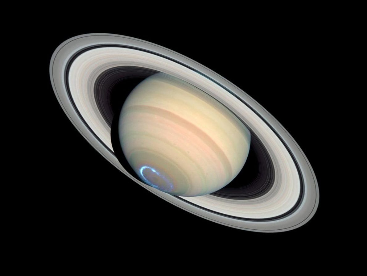 Streams of charged particles blasted from the sun collide with Saturn's magnetic field, creating an aurora ...