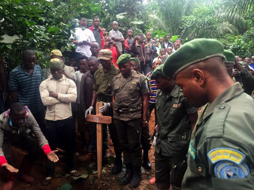 Okapi Wildlife Reserve park rangers watch as the bodies of their colleagues are lowered into the ground. The Democratic Republic of the Congo is one of the most dangerous places to be a ranger.