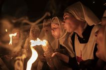 Nuns blow out their candles at the Holy Fire ceremony.