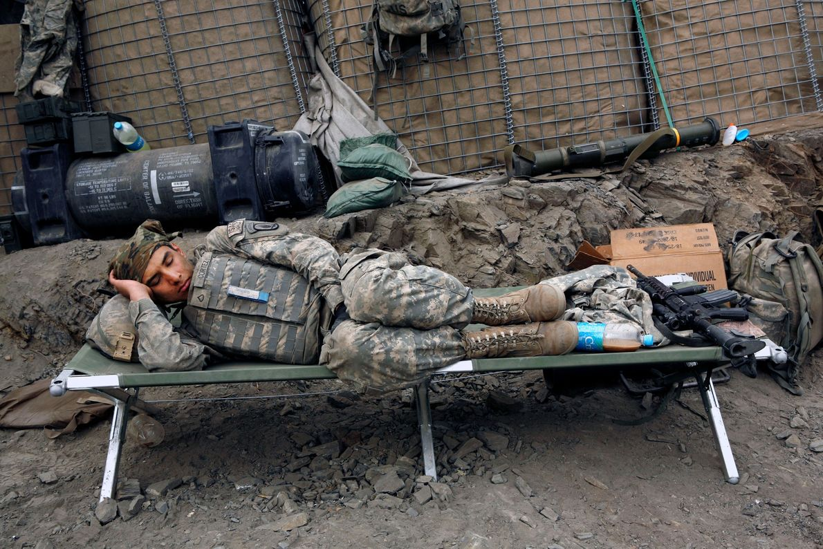 An American soldier sleeps following night duty at a frontline base in Afghanistan's Korengal Valley.