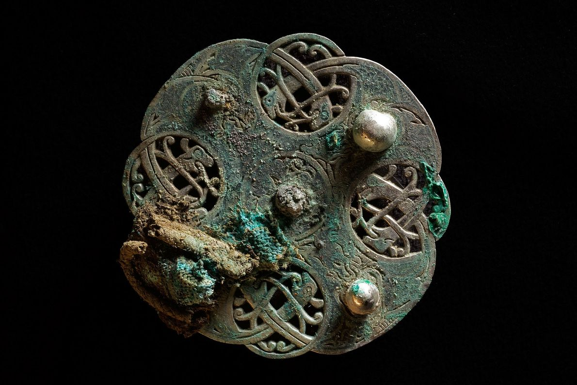 Intertwining snakes or serpents form an intricate design on a silver disk brooch from the hoard. ...