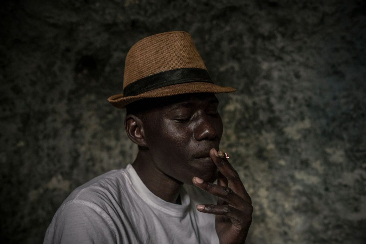 Mbacke, who lives in the caves for economic reasons, smokes tobacco inside his home.