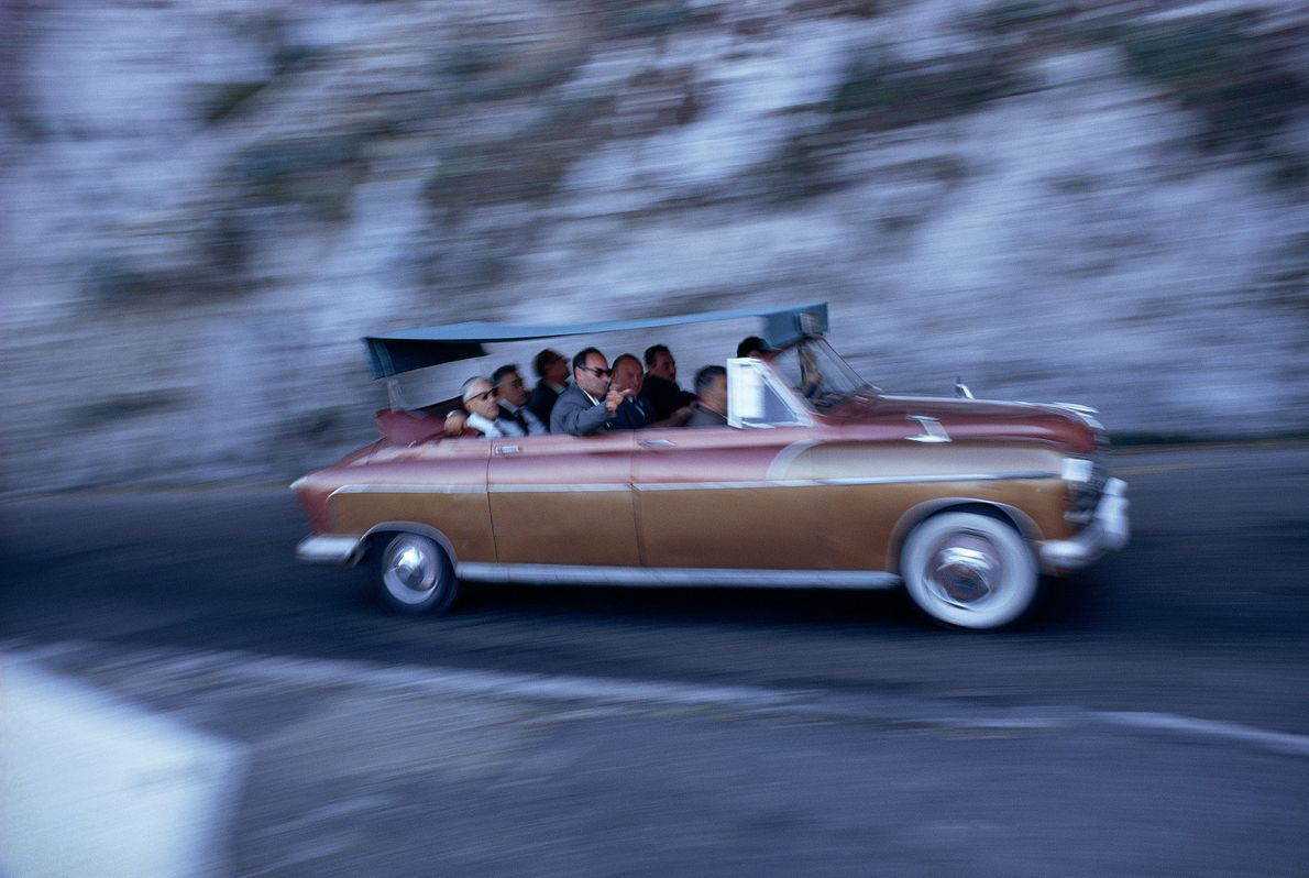 A covered convertible drives a joyful crowd to Anacapri.