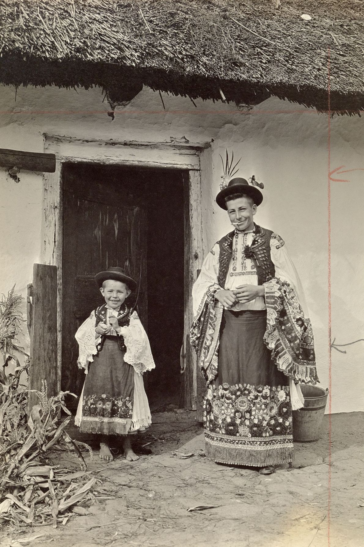 A father and son in similar traditional clothing pose for an informal portrait in Mezőkövesd, Hungary, ...