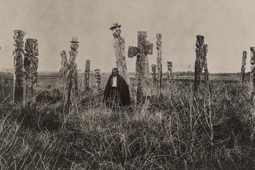 An Araucanian man stands in the middle of a graveyard in Chile.