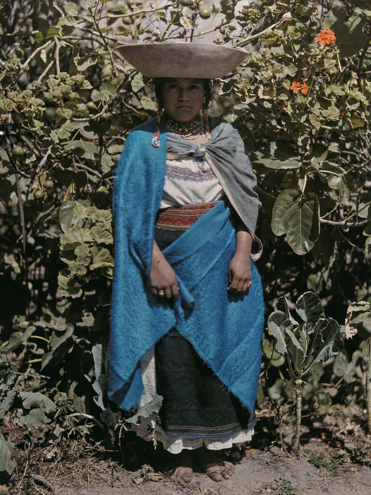 A woman posing in front of a plant in Ecuador wears a hat with a bowl-shaped ...