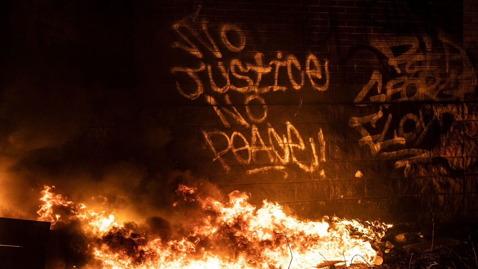 Graffiti expressing support for protesters marks the side of the 3rd Precinct building as it burns ...